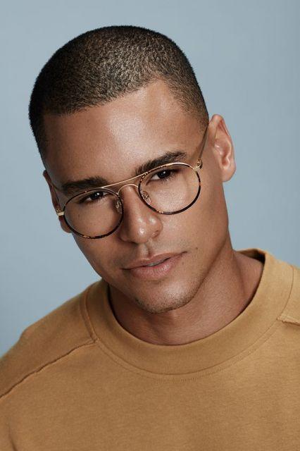 Homem com óculos aviador em formato redondo com armação fina.