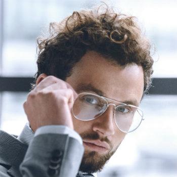 Foto do rosto de um homem de terno usando um óculos aviador masculino de grau.