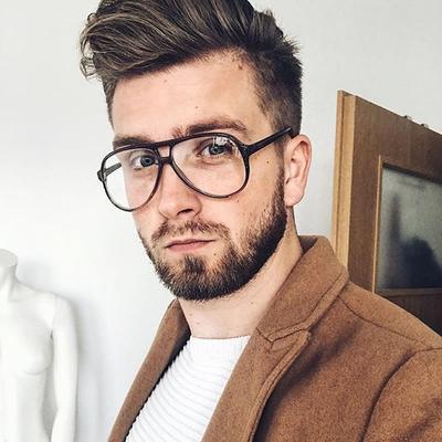 Homem com cabelo no estilo poumpador usando um óculos aviador de grau levemente arredondado.
