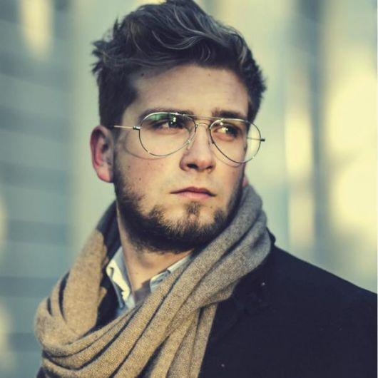 Homem com cachecol e trajes de frio. Ele usa um óculos aviador discreto com armação fina.