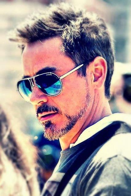 Robert Downey Jr. de perfil usando um óculos aviador com a lente azul espelhada.