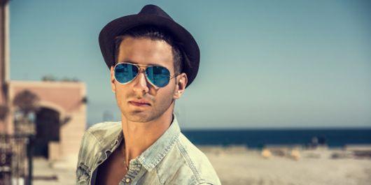 Homem de chapéu em uma praia com o fundo desfocado usando um óculos aviador com lente espelhada levemente azul.