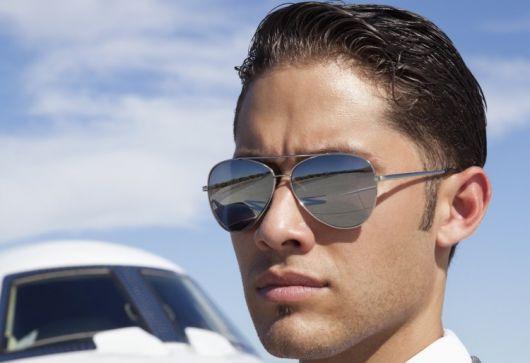 Foto do rosto de um homem com o cabelo penteado com gel usando um óculos aviador espelhado que reflete tudo que está a sua frente.