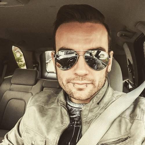 Homem dentro de um carro tirando uma selfie. Ele tem dois piercings na lateral do lábio inferior, cabelo penteado para o lado com gel e óculos aviador espelhado.