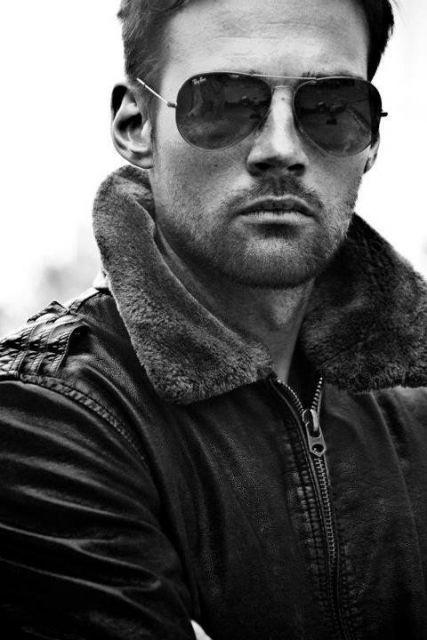 Homem com uma jaqueta fechada usando um óculos aviador escuro da Ray Ban.