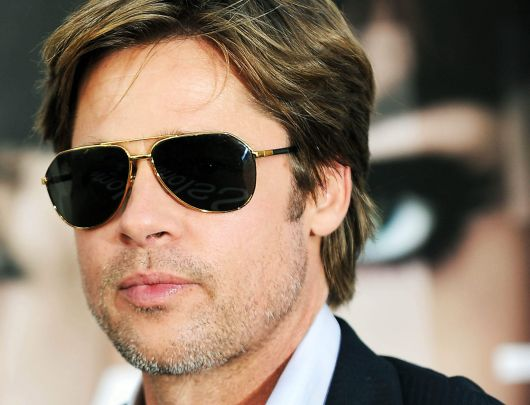 04b0aa500e5c9 Brad Pitt de terno usando um óculos aviador escuro com a armação dourada.