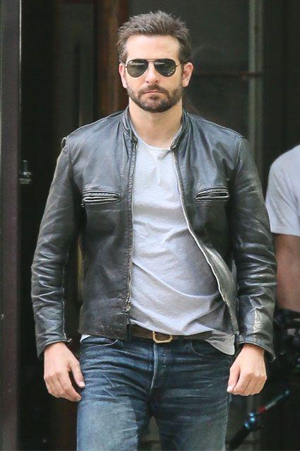Bradley Cooper andando na rua. Ele está vestindo uma jaqueta de couro, camiseta lisa, calça jeans e um óculos aviador escuro.