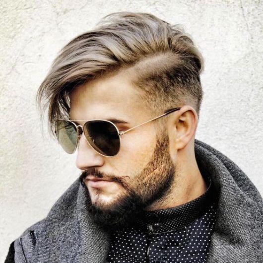 Foto de um homem de perfil. Ele tem a lateral do cabelo raspada com os fios grandes no topo e usa um óculos aviador escuro.