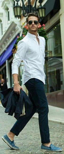 Homem andando na rua vestindo trajes sociais. Ele segura seu terno na mão e os botões superiores de sua camisa estão abertos. Ele também usa um óculos aviador escuro.