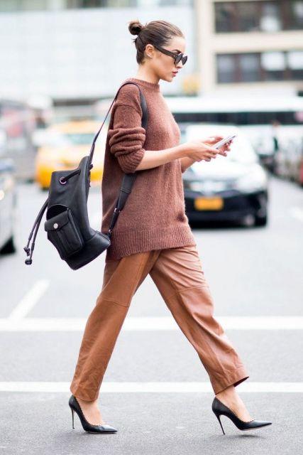 Modelo veste calça marrom, scarpin preto e sueter caramelo com mochila preta.