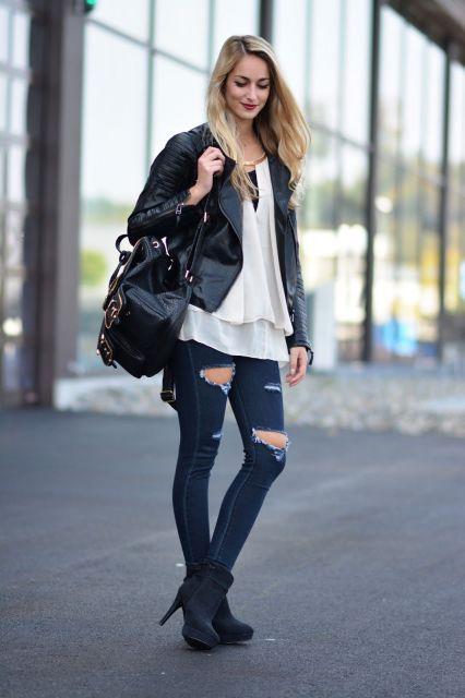 Modelo usa calça destruída no joelho jeans, bota preta, camiseta branca e jaqueta preta com mochila na mesma cor.