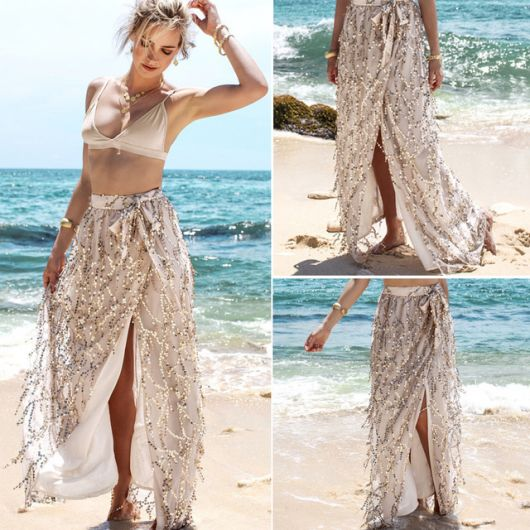 Modelo veste saia longa sapida de praia nude com biquini na mesma cor.