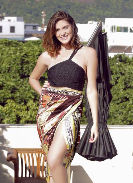 Modelo usa maio preto com canga saia estampada.