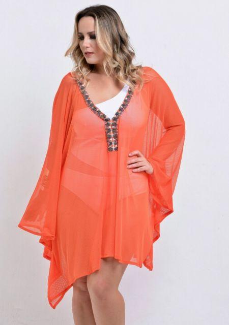 Modelo veste saída de praia laranja com biquini branco plus size.