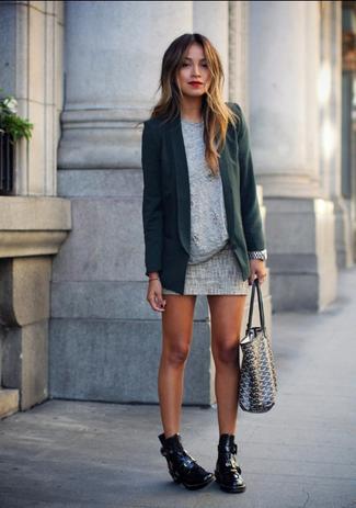 Modelo usa vestido cinza curto de inverno com casaco verde e botinha preta.