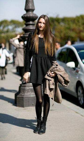 Modelo veste vestido preto com botinha preta.