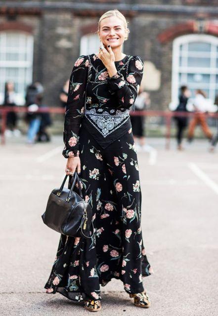 Modelo usa vestido longo floral preto.