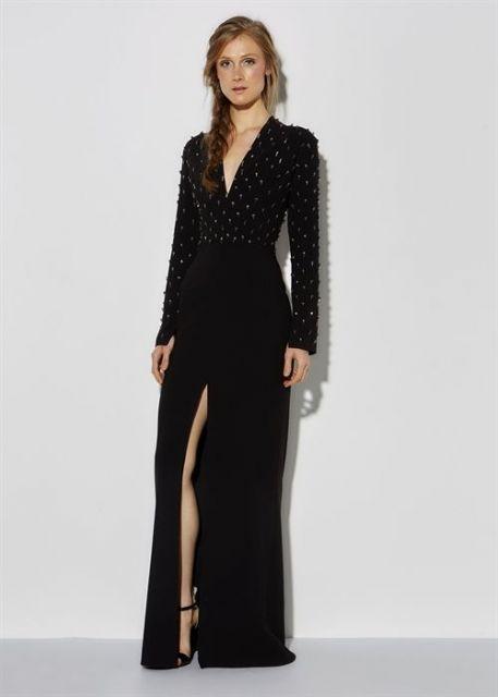 Modelo usa vestido longo preto com decote e fenda na cor preta.