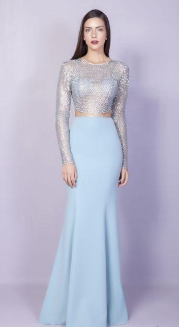 Modelo usa vestido azul claro longo com transparencia e de mangas longas.