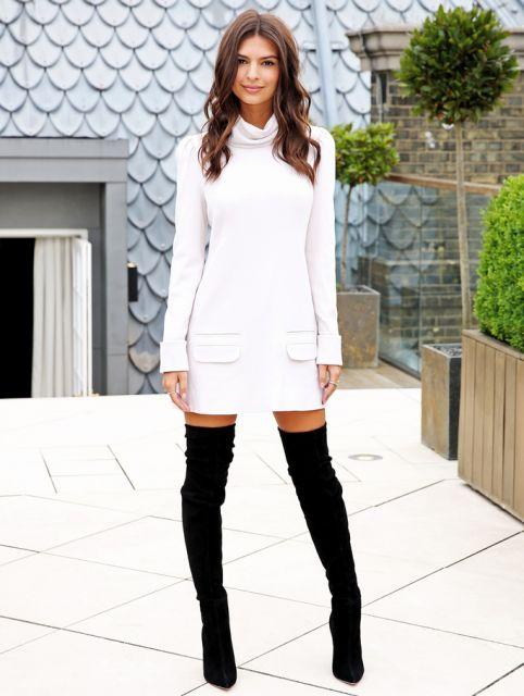 Modelo usa vestido branco com botas pretas de cano longo.