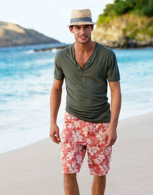 Homem caminhando na praia. Ele veste um chapéu, uma camiseta lisa e uma bermuda florida com bastante flores, mas poucas cores, apenas branco e vermelho.