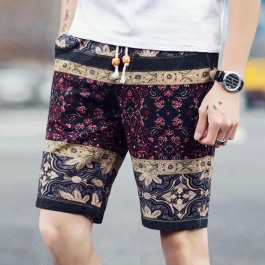 Foto das pernas de um homem com bermuda florida masculina. Ela tem um tecido leve e três camadas diferentes de estampas baseadas em formas geométricas.