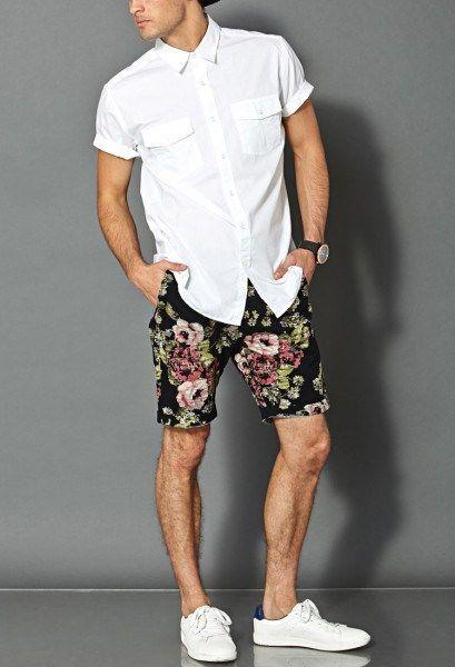 Foto de um homem com uma camisa branca simples e uma bermuda florida com  fundo preto 36dcbafb089b8
