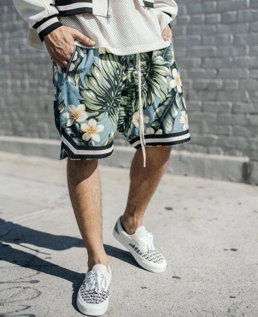 Foto da perna de um homem vestindo uma bermuda florida que termina na altura do joelho e um tênis com estampa de pequenos quadriculados preto e branco.