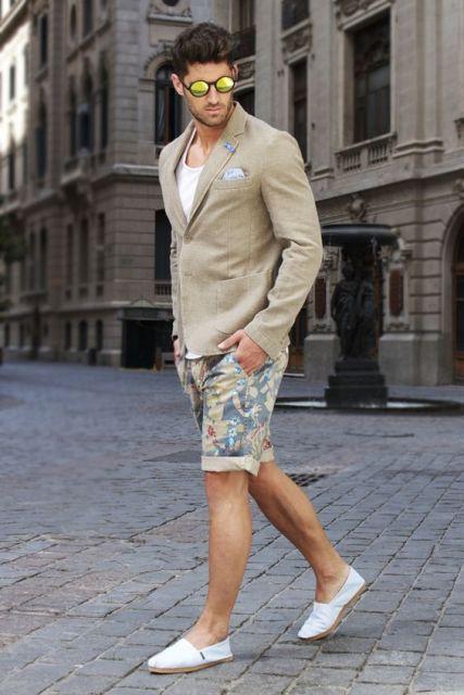 Homem caminhando na rua vestido com um blazer, bermuda florida dobrada na extremidade e um sapatênis alpargatas.