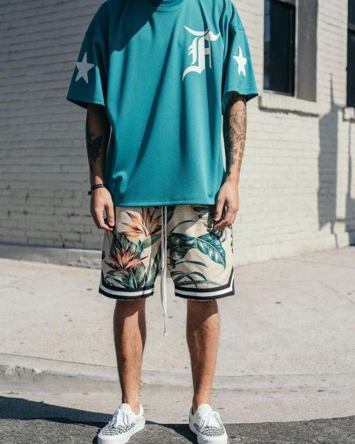 Foto do pescoço até o calcanhar de um homem tatuado vestindo uma bermuda florida masculina acompanhada de uma camiseta larga sem detalhes de estampa, apenas um F no peito e duas estrelas, uma em cada manga.