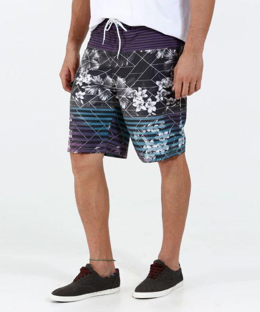Foto das pernas de um homem vestindo uma bermuda florida com listras nas estampa.