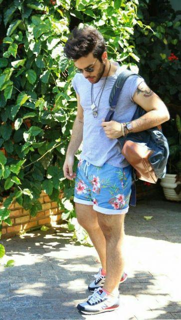 Homem com uma mochila nas costas olhando para baixo. Ele veste uma camiseta de mangas curtas, um tênis de corrida e uma bermuda florida curta dobrada na extremidade.