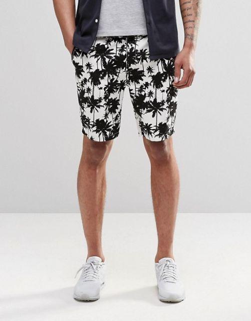 Foto das pernas de um homem em um fundo branco. Ele veste uma bermuda com coqueiros pretos em um tecido branco.