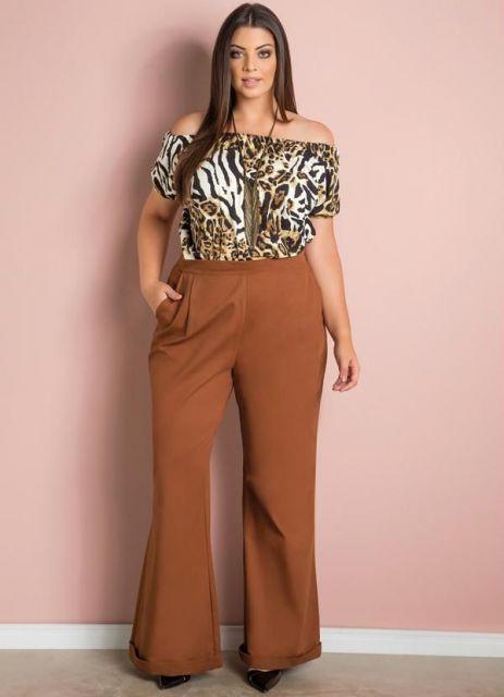 Modelo usa calça pantalona marrom, blusa estampada tigresa e sapato de salto.
