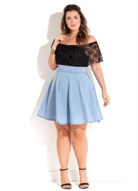 Modelo usa saia azul de pregas, sandalia preta e blusa de renda preta.