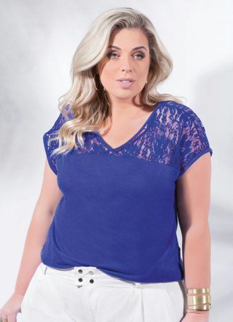 Modelo usa blusa azul com renda e calça branca.