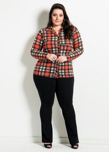 Modelo veste calça preta, sandalia na mesma cor e blusinha plus size xadrez vermelho com branco.