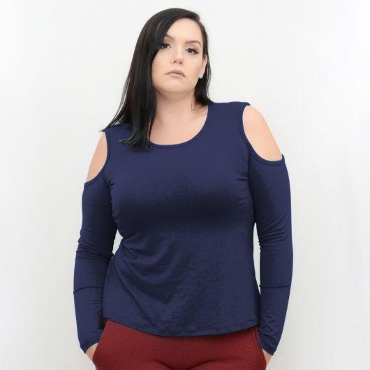 Modelo usa calça vermelha de bolsos com blusa azul plus size de ombros vazados manga longa.