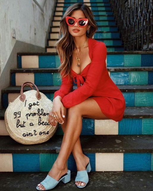 Modelo veste vestido vermelho com sandalinha azul, óculos escuros e bolsa redonda de palha.