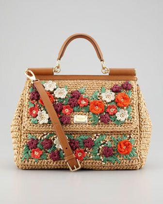 Bolsa de palha com flores de crochê coloridas.