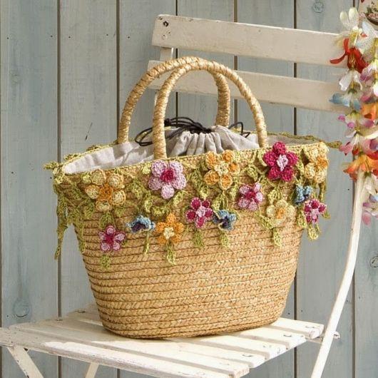 Modelo de bolsa de palha com flores artificiais na borda.