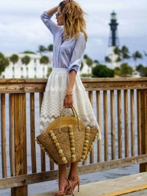 Modelo veste saia branca midi com camisa azul, sandalia e bolsa de praia.