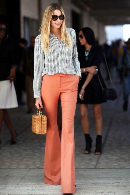 Modelo usa calça laranja, camisa listrada e bolsa de palha.