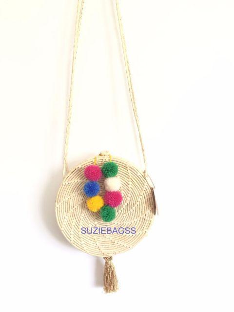 Modelo de bolsa redonda com pompons.