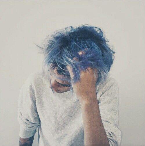 Homem de cabelo azul em fundo branco passando a mão entre os fios bagunçados.