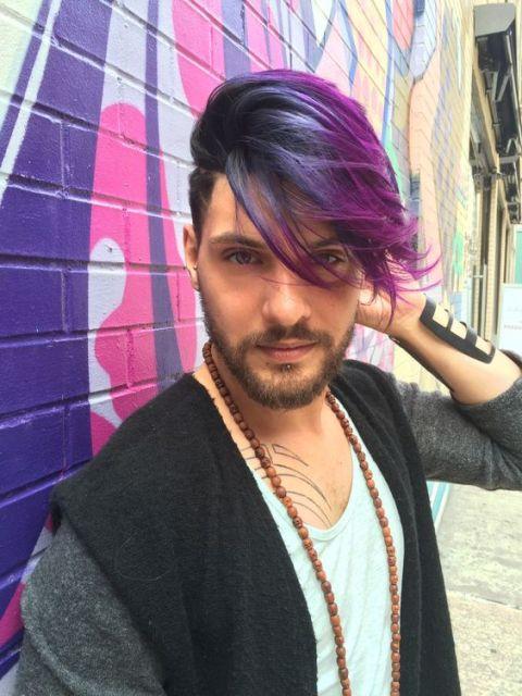 Homem em frente a um muro grafitado. Seu cabelo é longo no topo, jogado para o lado e raspado nas laterais. Os fios superiores são pintados com tons de azul e roxo.