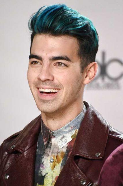 Homem com topete pintado com tons suaves de verde e azul.