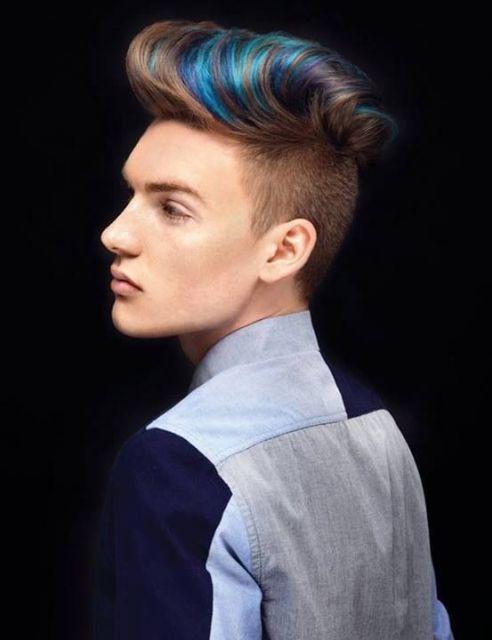 Homem de perfil com um corte pompadour onde o topete é tingido levemente com luzes azuis.