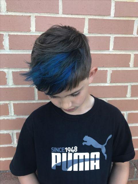 Menino em frente a uma parede de tijolos expostos olhando para baixo. Seu cabelo tem dois pontos com luzes azuis na franja.