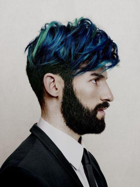 Homem de perfil com a lateral do cabelo raspada e os fios de cima longos formando uma franja, que também são pintado com luzes azuis e verdes.